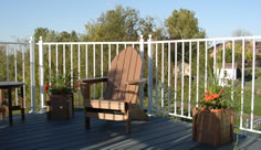 Residential colonial picket aluminum railing photo with composite chairs and planters by Versadeck Decking