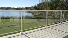 Residential glass aluminum railing photo with light clay modular aluminum decking and a view of a lake by Versadeck Decking